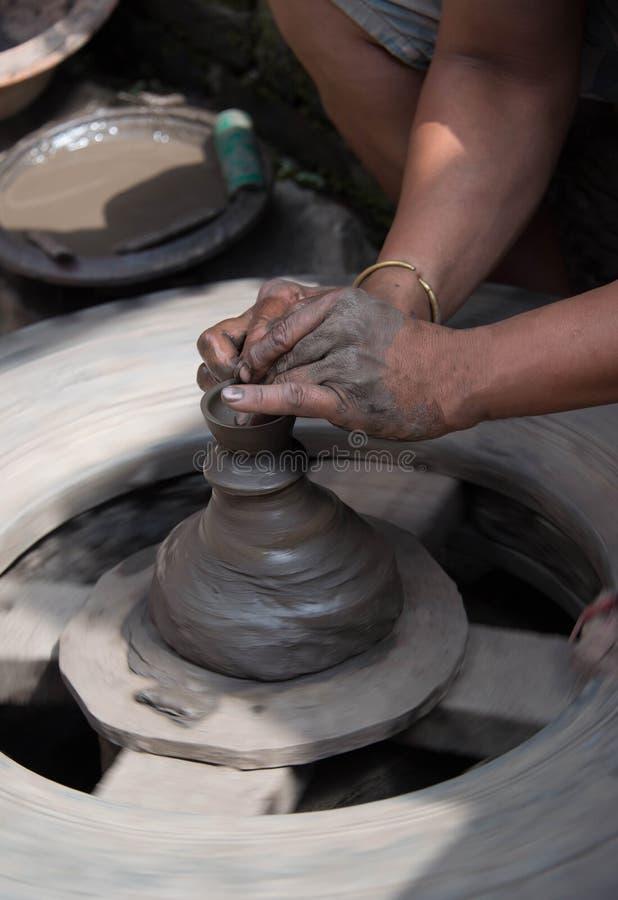 Mains de potiers sur la roue de potiers faite maison ouvrant un pot en céramique d'argile photographie stock libre de droits