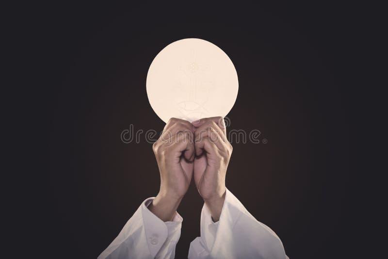 Mains de prêtre soulevant un pain de communion photographie stock libre de droits