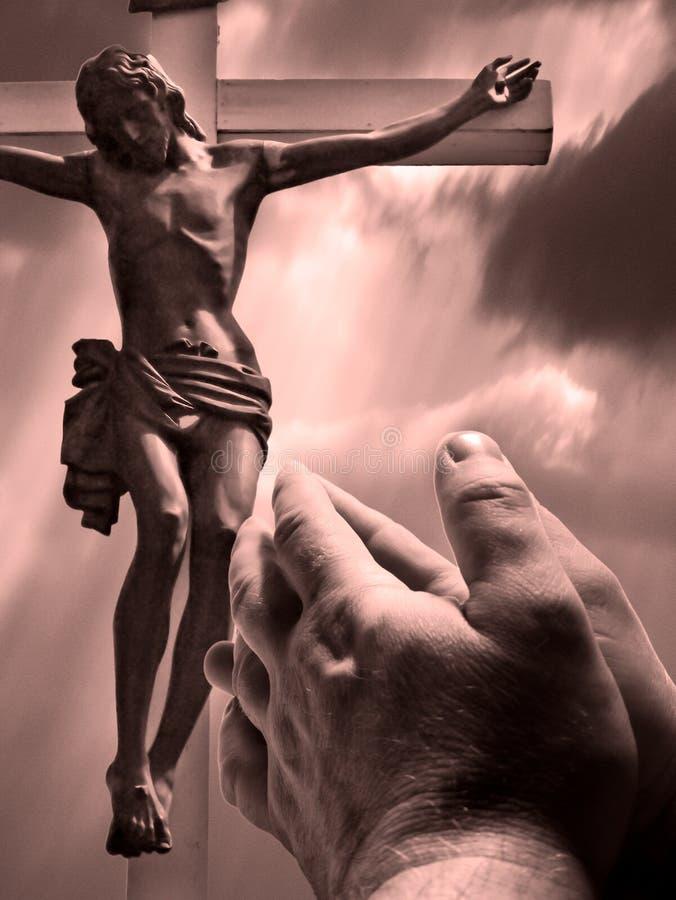 Mains de prière avec la croix images libres de droits