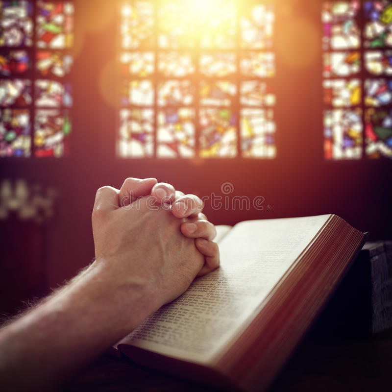 Mains de prière sur une bible sainte image libre de droits