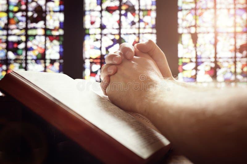 Mains de prière sur une bible sainte photo stock