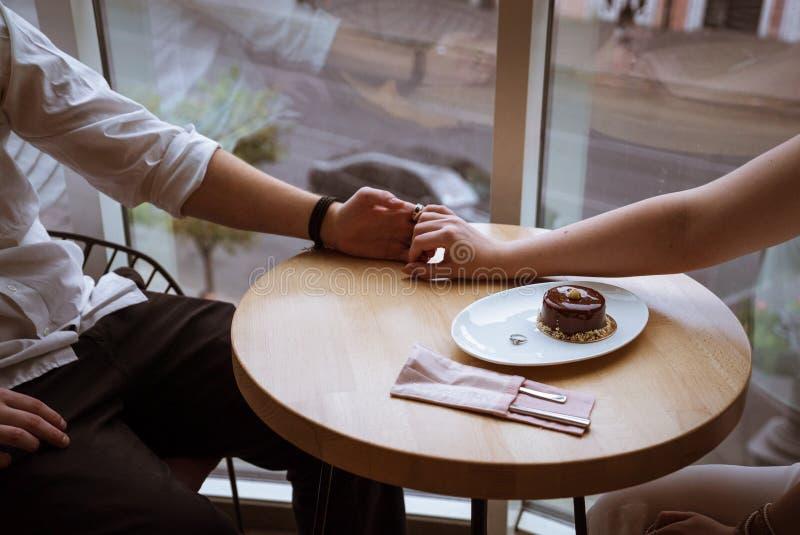 Mains de prise de garçon et de fille en café images stock