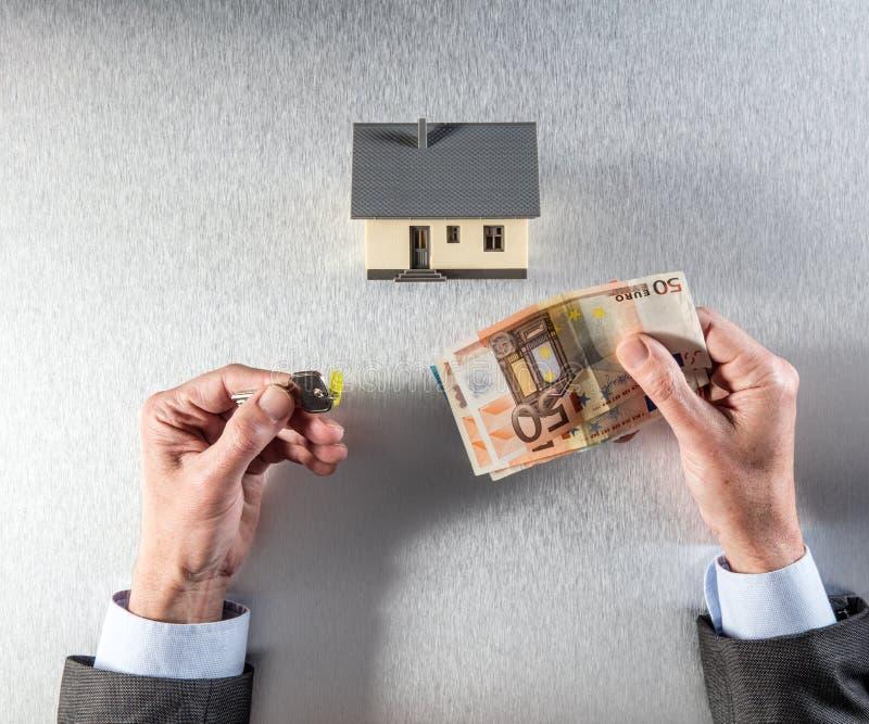 Mains de professionnel de propriété donnant une clé et un argent liquide de maison image stock
