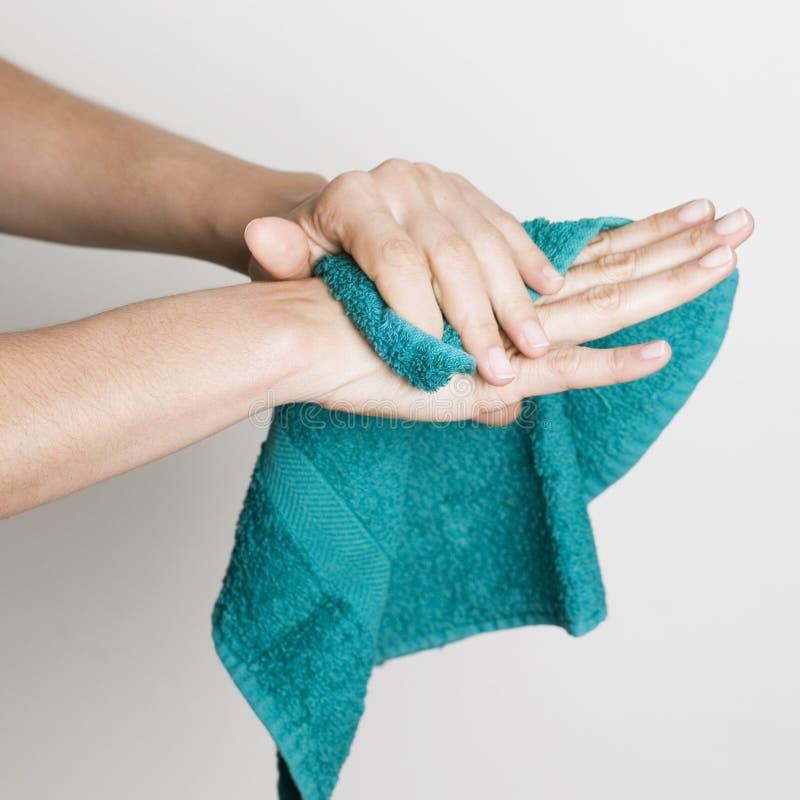 Mains de séchage avec un essuie-main photographie stock