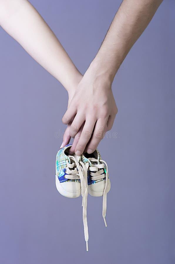 Mains de s'attendre à des parents tenant une paire d'espadrilles de bébés garçon images stock