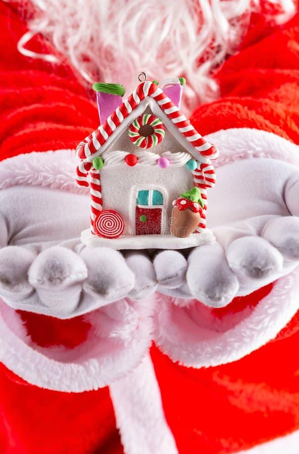 Mains de Santa Claus tenant un modèle de maison photos libres de droits