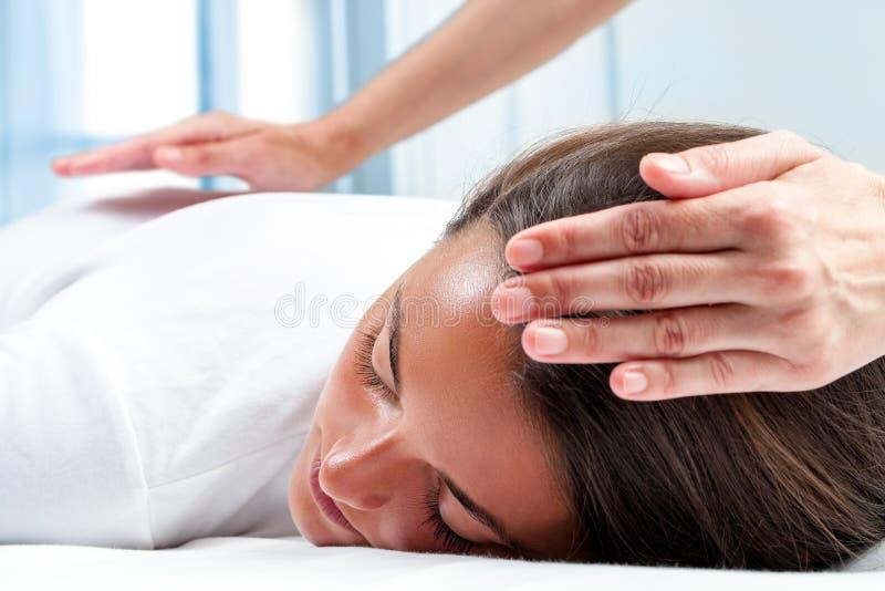 Mains de thérapeutes faisant la thérapie de reiki sur la fille photographie stock