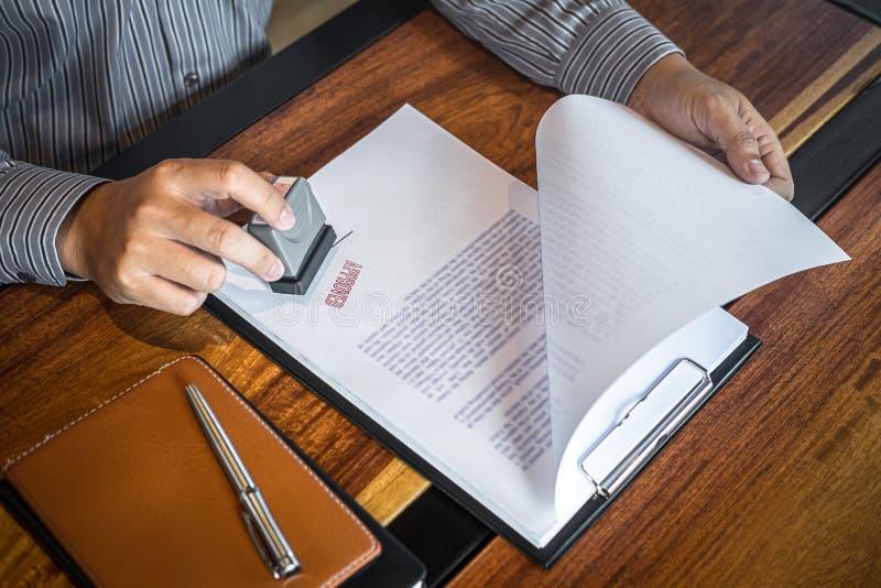 Mains de timbre d'homme d'affaires sur le document sur papier pour approuver l'accord contractuel d'investissement productif image libre de droits