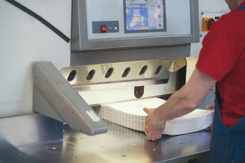 Mains de travailleur dans la typographie travaillant à la machine de guillotine de coupeur images stock