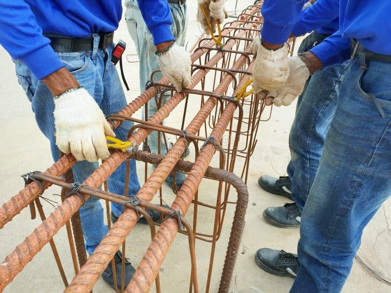 Mains de travailleurs utilisant le fil d'acier pour fixer des barres d'acier avec le fil machine pour le renfort photo libre de droits