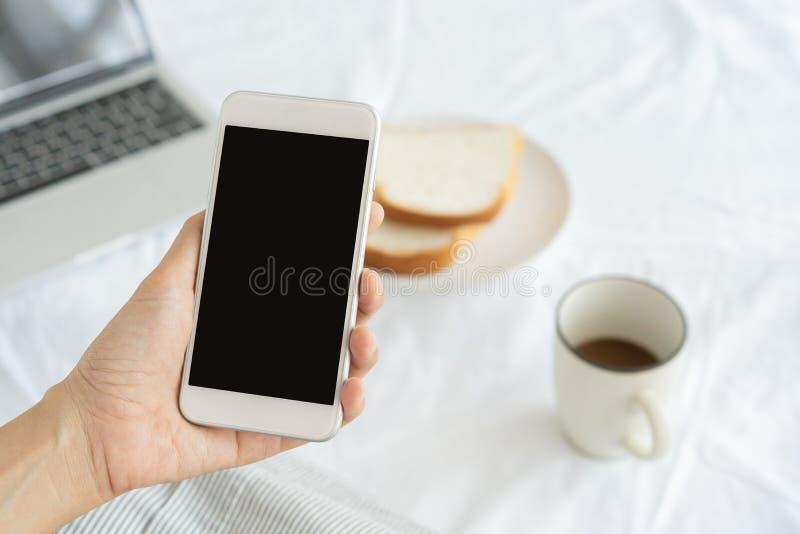 Mains de travailleuse active tenant et ? l'aide du t?l?phone intelligent sur le fond de bureau Sur le bureau ayez le caf?, les pa photos stock