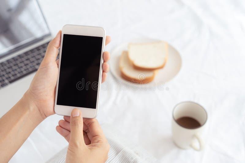 Mains de travailleuse active tenant et ? l'aide du t?l?phone intelligent sur le fond de bureau Sur le bureau ayez le caf?, les pa image stock