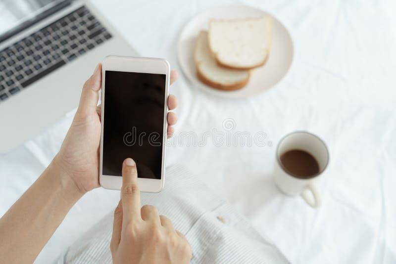 Mains de travailleuse active tenant et ? l'aide du t?l?phone intelligent sur le fond de bureau Sur le bureau ayez le caf?, les pa images stock