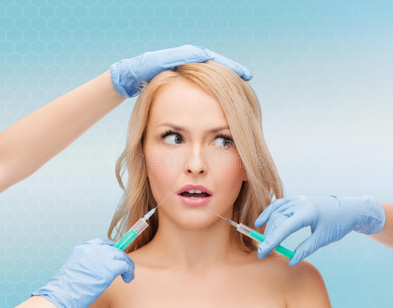 Mains de visage et d'esthéticien de femme avec des seringues images stock
