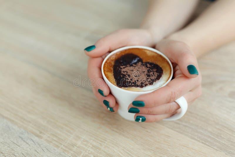 Mains de vue supérieure tenant la tasse de café blanche copie de coeur sur le café image stock