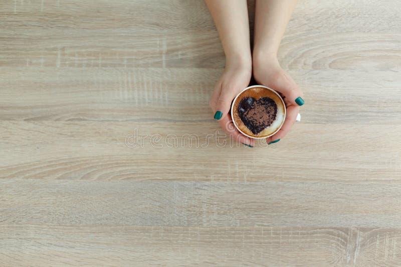 Mains de vue supérieure tenant la tasse de café blanche copie de coeur sur le café images stock