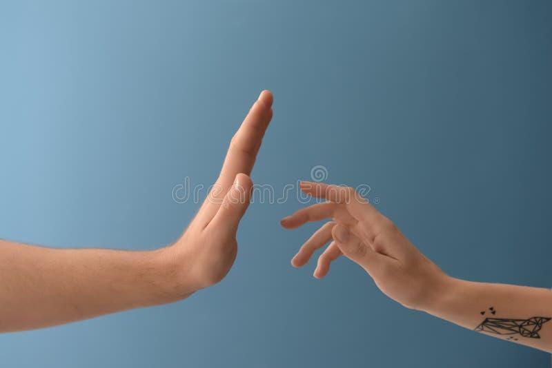 Mains des ajouter à l'apparence de l'homme arrêtant le geste sur le fond de couleur image stock