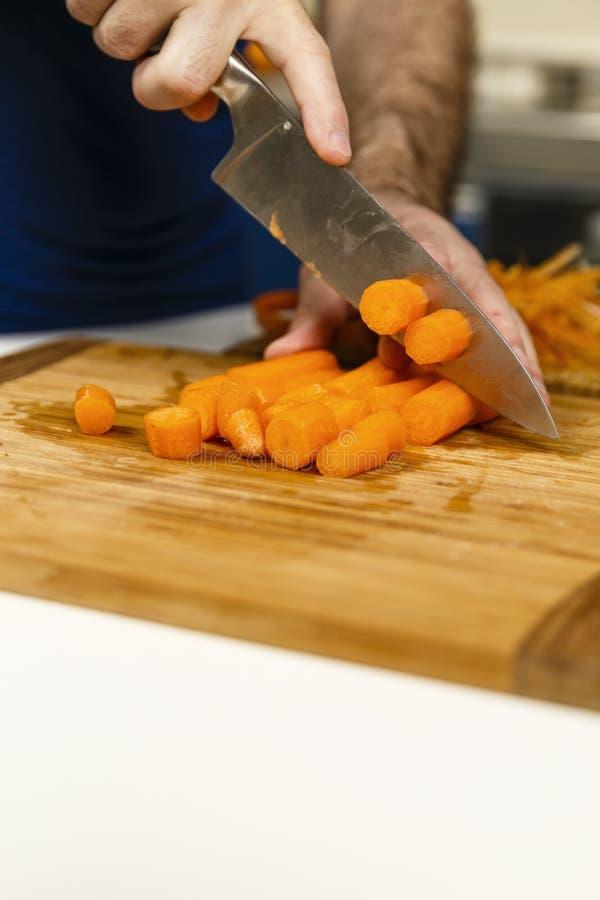 Mains des carottes épluchées par coupe de chef photo libre de droits
