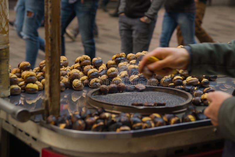 Mains des châtaignes de marchand ambulant Châtaignes rôties dans des marchands ambulants Nourriture populaire parmi des touristes images libres de droits