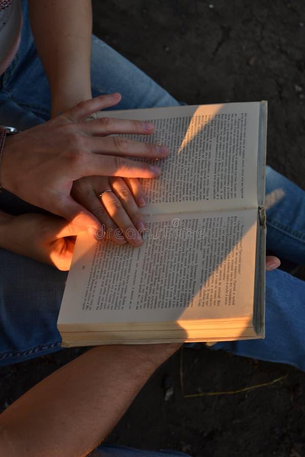 Mains des couples dans l'amour tenant un livre photos stock