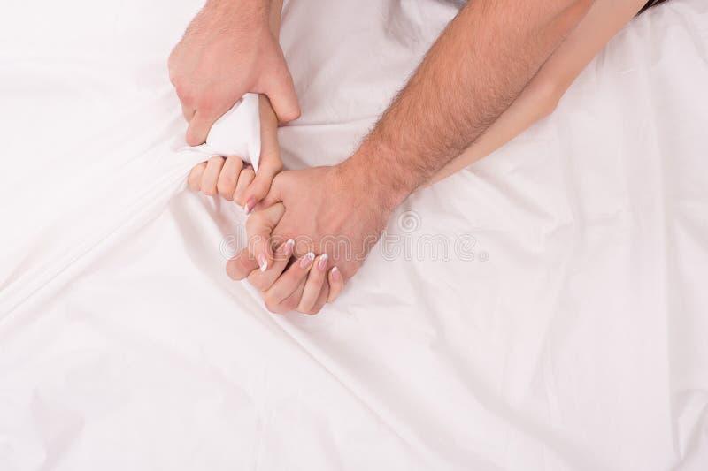 Mains des couples que la fabrication de l'amour dans le lit sur le blanc a chiffonné la feuille, foyer sur des mains photographie stock libre de droits