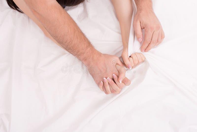 Mains des couples qui faisant l'amour sur la feuille chiffonnée blanche, foyer sur des mains photo libre de droits