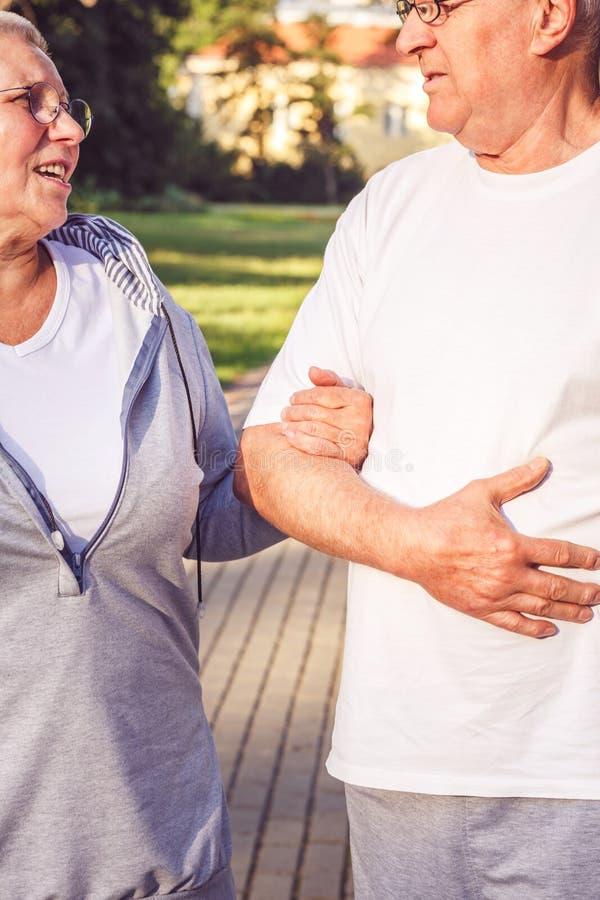 Mains des couples supérieurs pendant la promenade en parc le jour ensoleillé image stock