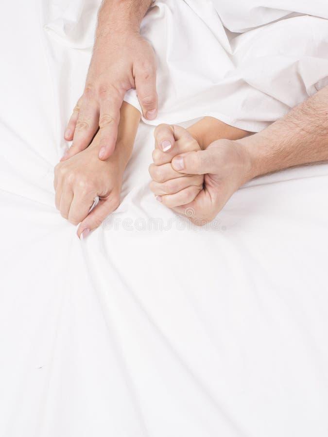 Mains des couples tirant les feuilles blanches dans la convoitise et l'orgasme image libre de droits