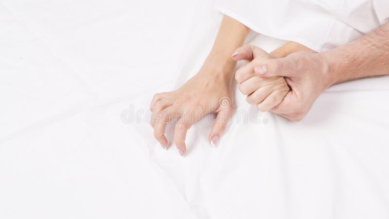 Mains des couples tirant les feuilles blanches dans la convoitise et l'orgasme photos libres de droits