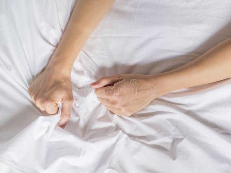 Mains des femmes tirant les feuilles blanches dans la convoitise et l'orgasme images libres de droits