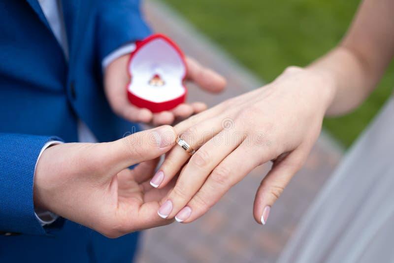 Mains des jeunes mariés avec l'anneau, cérémonie de mariage extérieure photographie stock libre de droits