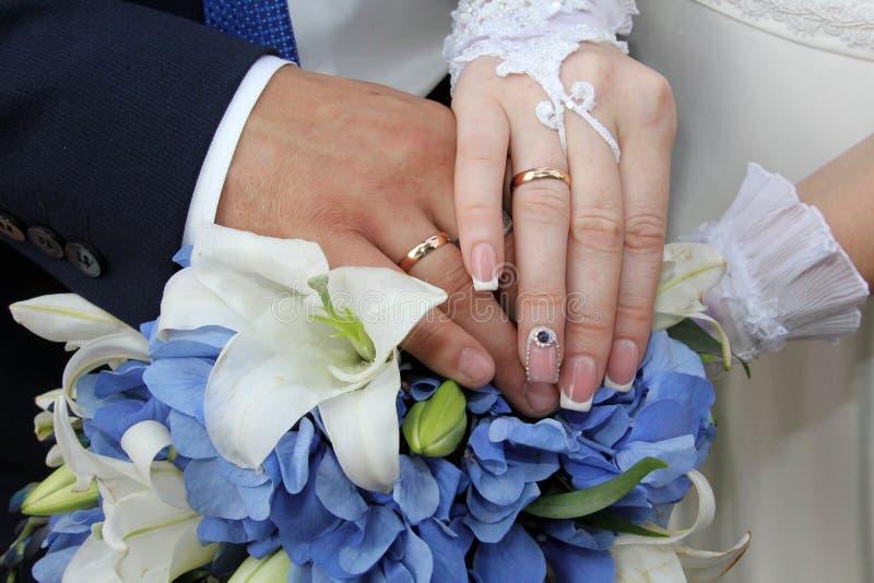 Mains des jeunes mariés sur un bouquet nuptiale photographie stock