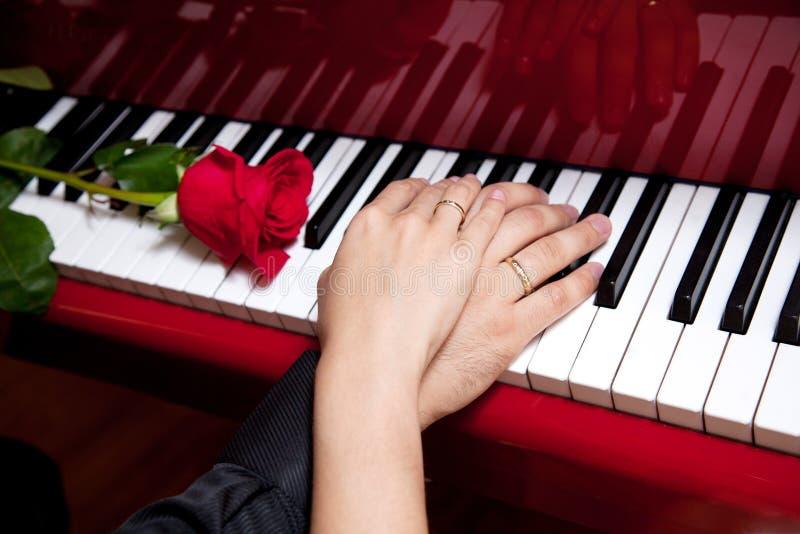 Mains des ménages mariés sur le piano image stock