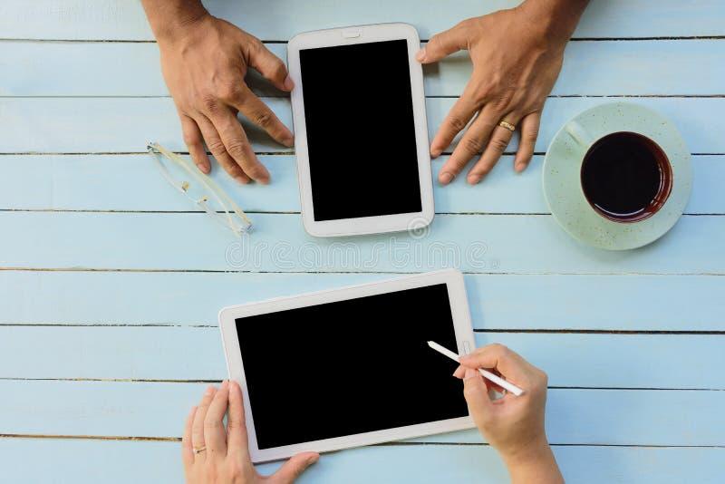 Mains des mains du ` s des hommes et de femmes utilisant la tablette Vue supérieure image libre de droits