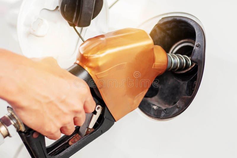 Mains distribuant le carburant pour des voitures photo libre de droits