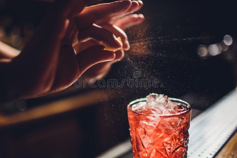 Mains du barman s arrosant le jus dans le verre de cocktail rempli de boisson alcoolis?e sur le fond fonc? images libres de droits