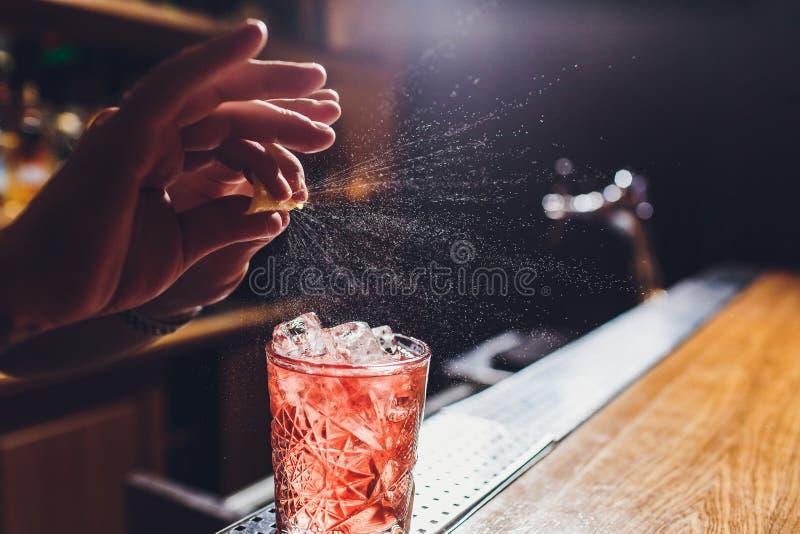 Mains du barman s arrosant le jus dans le verre de cocktail rempli de boisson alcoolis?e sur le fond fonc? photos libres de droits