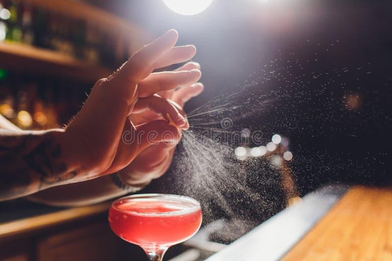 Mains du barman s arrosant le jus dans le verre de cocktail rempli de boisson alcoolis?e sur le fond fonc? photo stock