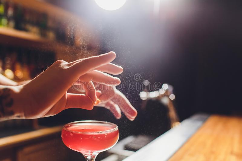 Mains du barman s arrosant le jus dans le verre de cocktail rempli de boisson alcoolis?e sur le fond fonc? image stock