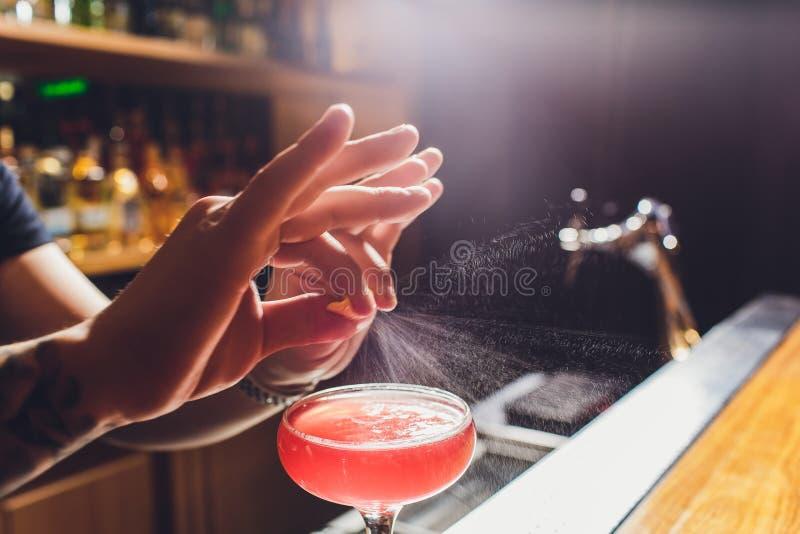 Mains du barman s arrosant le jus dans le verre de cocktail rempli de boisson alcoolis?e sur le fond fonc? photos stock