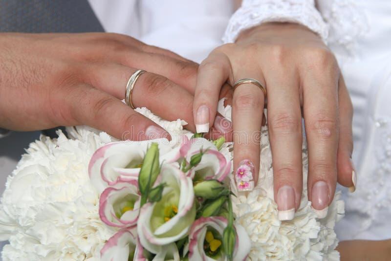 Mains du bouquet de mariage de jeune mariée et de demoiselle d'honneur photos libres de droits