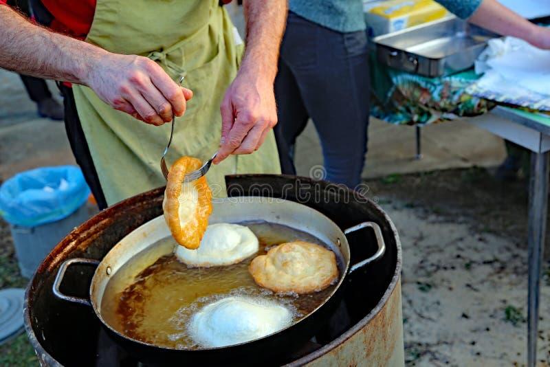 Mains du cuisinier expert tout en faisant frire quelques crêpes délicieuses dessus photo libre de droits