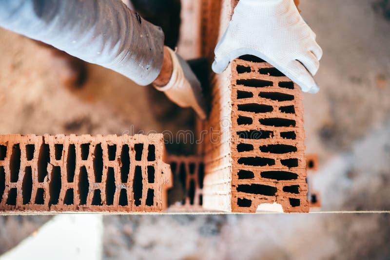 mains du maçon masculin industriel installant des briques sur le chantier de construction image stock