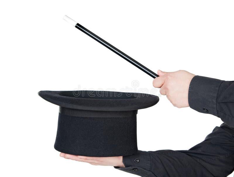Mains du magicien avec la baguette magique magique et le premier chapeau image libre de droits