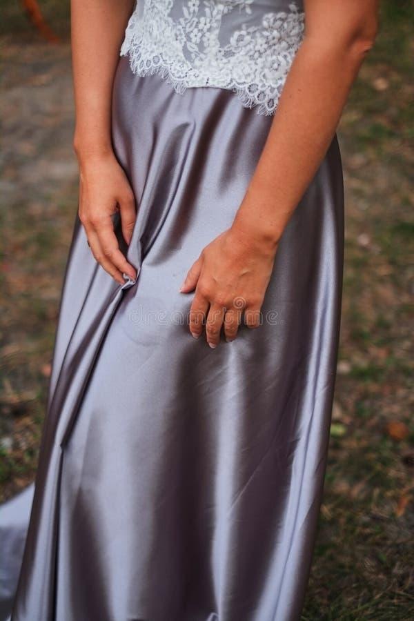 mains du mensonge de jeune mariée sur une robe pourpre en soie images stock