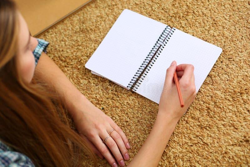 Mains du mensonge femelle blond sur la moquette tenant le crayon photos libres de droits