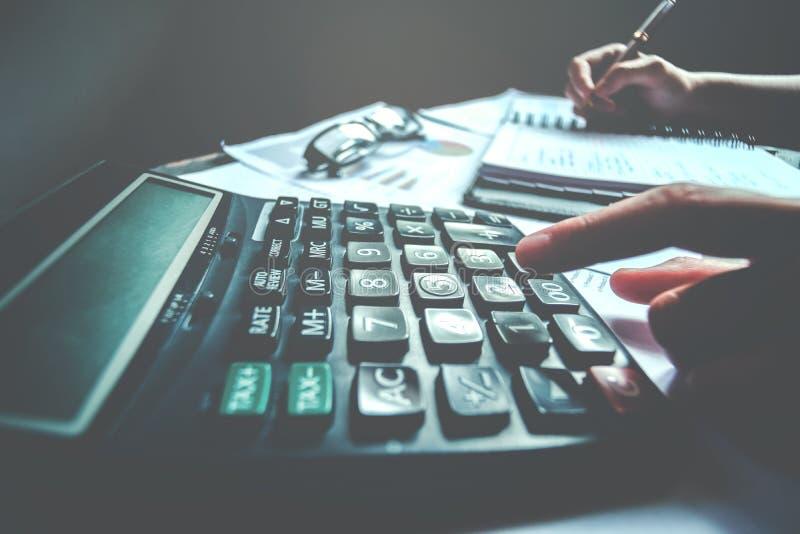 Mains du ` s d'homme d'affaires avec la calculatrice au bureau et financier photos libres de droits