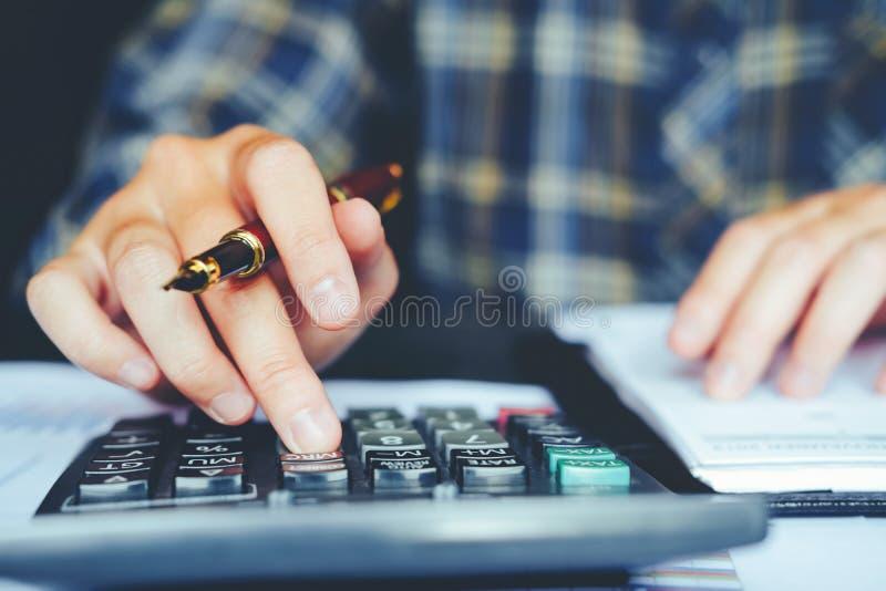 Mains du ` s d'homme d'affaires avec la calculatrice au bureau et financier images libres de droits