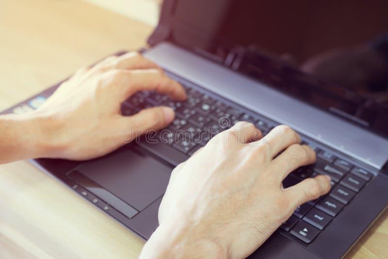 Mains du ` s d'homme dactylographiant sur l'ordinateur portable photographie stock