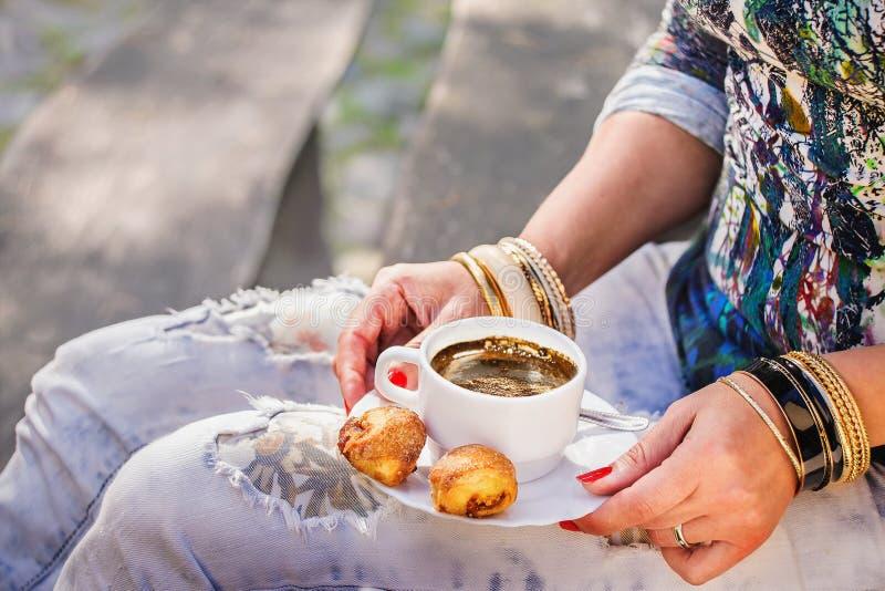 Mains du ` s de femme avec les bracelets d'or, la tasse de café et le casse-croûte image stock